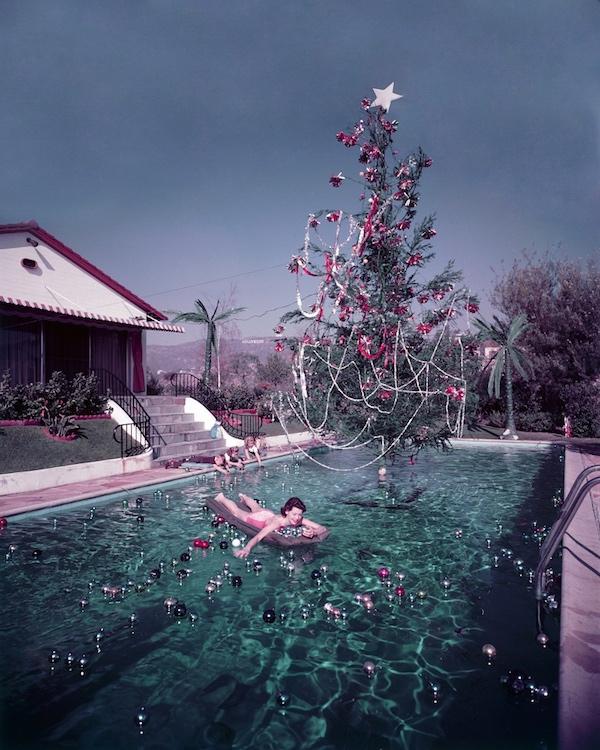 Rita Aarons, moglie del fotografo Slim Aarons, su un materassino in piscina con le decorazioni natalizie, in lontananza si può scorgere la scritta Hollywood 1954 (Photo by Slim Aarons/Hulton Archive/Getty Images)