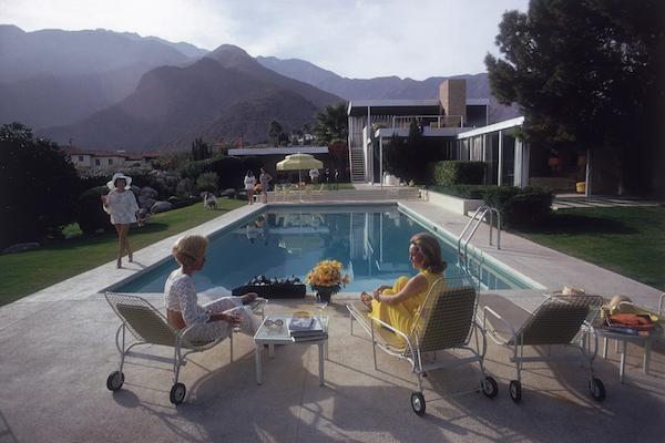 ALa celebre casa a Palm Springs progettata da Richard Neutra per Edgar Kaufman. Lita Baron siede accanto a Nelda Linsk a destra, la moglie del mercante d'arte Josef Linsk che sta parlando con un amica Helen Dzo Dzo in fondo alla piscina 1970 (Photo by Slim Aarons/Getty Images)