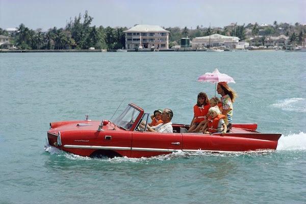 """Il produttore cinematografico Kevin McClory porta la moglie Bobo Sigrist e la loro famiglia a fare un giro in un """"Amphicar"""" attraverso il porto al Nassau 1967"""