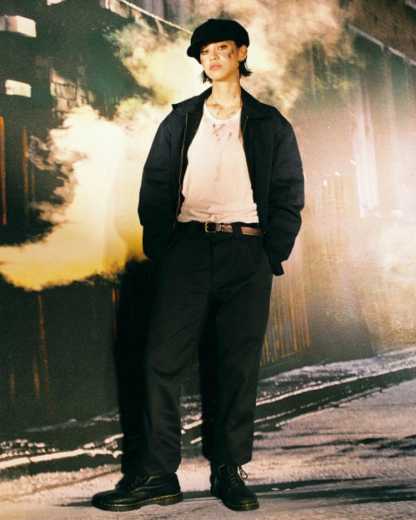 Una modella indossa un paio di chinos, la coppola e le classiche Dr. Martens. Credits: MoMA